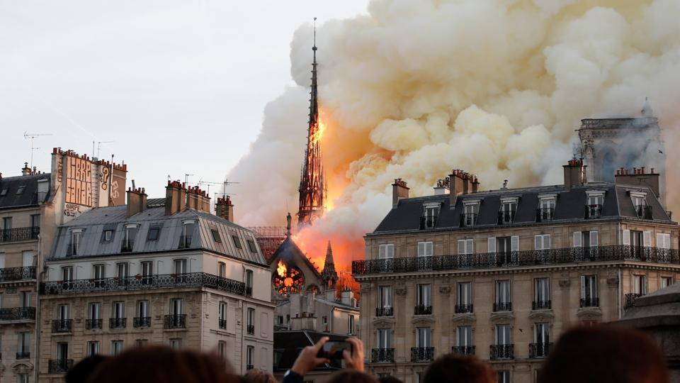 Smoke billows as fire engulfs the spire of Notre Dame Cathedral in Paris, France.
