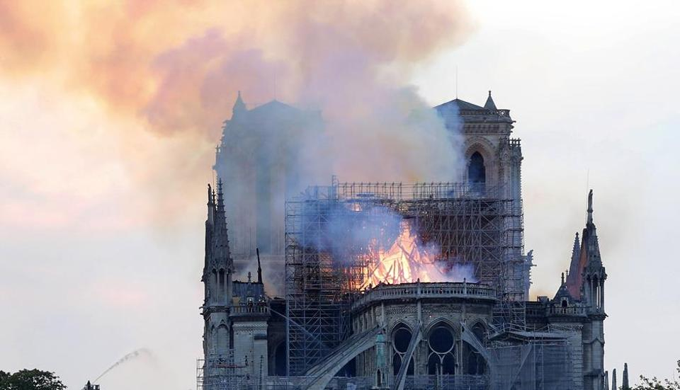 Flames and smoke rise from Notre Dame cathedral as it burns in Paris on  Monday,