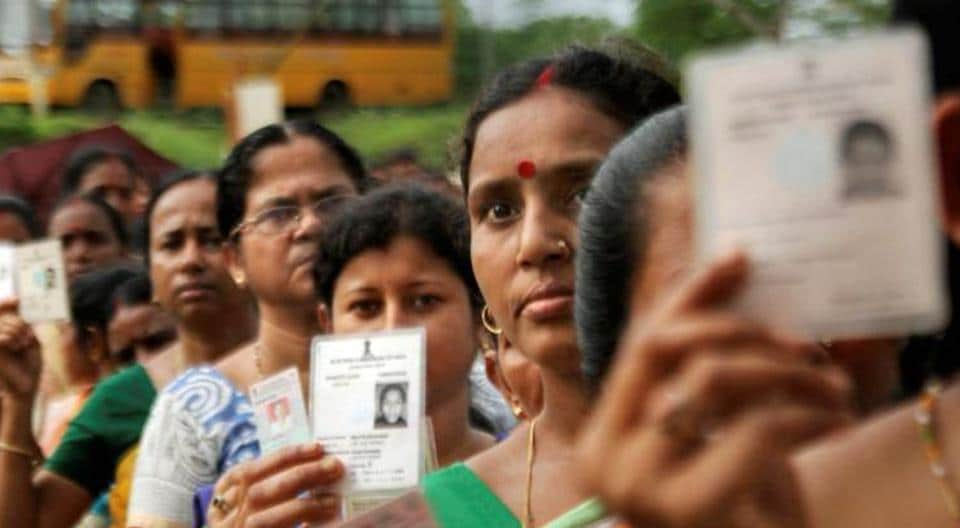 Women show their voter identity cards as they stand in a queue before casting their votes during the first phase of the general elections at a polling station in Agartala, Tripura on April 11, 2019.