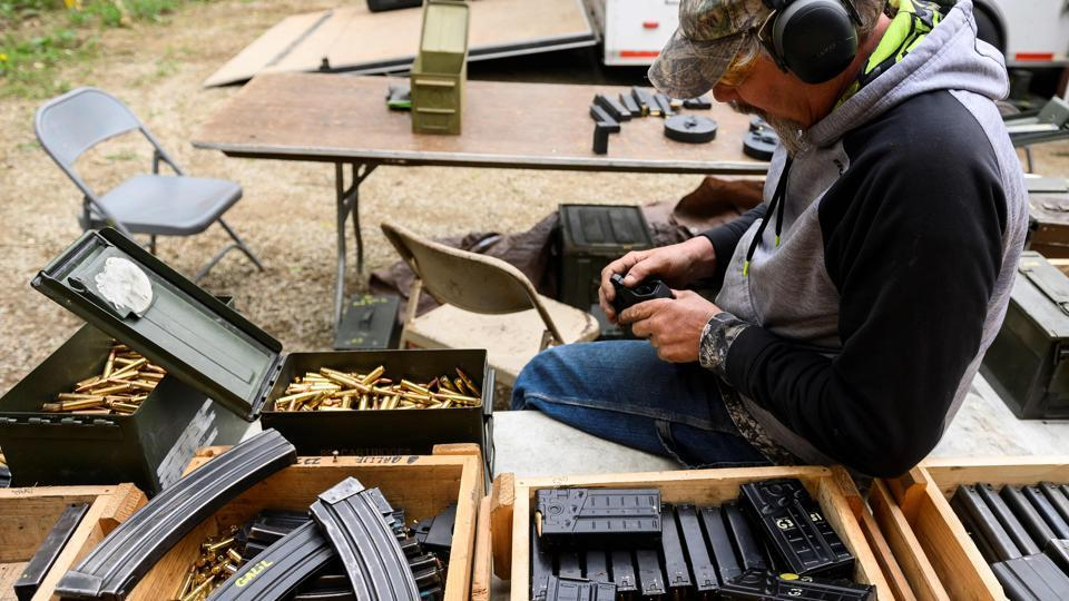 A man loads ammunition into clips at a machine gun rental stand during the Knob Creek Machine Gun Shoot and Military Gun show. The two-day event is held twice a year in the hills of Kentucky near the hamlet of West Point. (Andrew Caballero-Reynolds / AFP)
