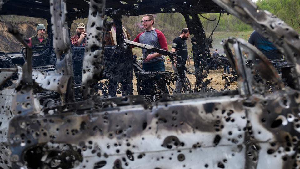 People look at a destroyed car on the main firing line. Kenny Sumner is the current owner and manager of the Knob Creek Gun Range. (Andrew Caballero-Reynolds / AFP)