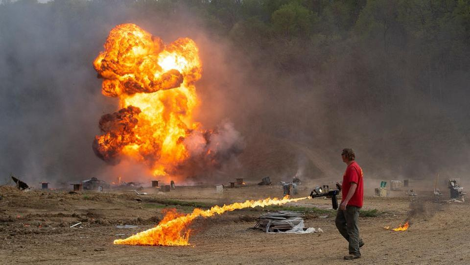 An employee uses a flame thrower as an explosion goes off during a shooting session. The Knob Creek Machine Gun Shoot and Military Gun Show was started in 1965 by Biff Sumner and a few friends who were having a cookout and firing off weapons for fun. (Andrew Caballero-Reynolds / AFP)