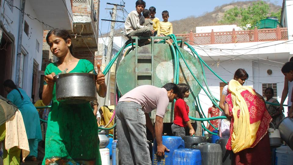 People collect water from a tanker in a Jaipur colony.