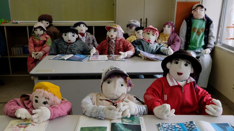 The secret to breathing life into the dolls? Applying pink colour to the lips and cheeks with a make-up brush, revealed Ayano. At the local school, she has placed 12 colourful child-sized dolls at desks, positioned as if part of a lively class poring over their books. The school closed seven years ago as there was no one left to teach, she recalled sadly. (Kazuhiro Nogi / AFP)