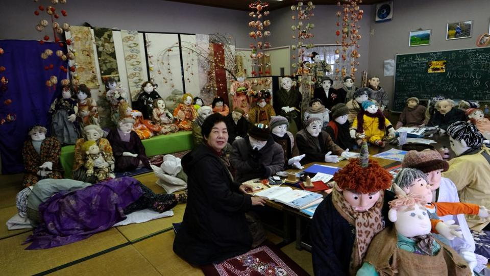 "Tsukimi Ayano with life-size dolls in her workshop. While there is little evidence of citizens returning to Nagoro, Ayano's dolls have attracted flesh-and-blood people from as far afield as the US and France. ""Before I started making scarecrows, nobody stopped by. Now many people visit here,"" she said. (Kazuhiro Nogi / AFP)"
