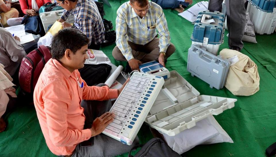 Uttar Pradesh, April 17 (ANI): Polling officials checking Electronic Voting Machine (EVM) at distribution center before leaving Second Phase of Lok Sabha election, in Mathura on Wednesday. (ANI Photo)