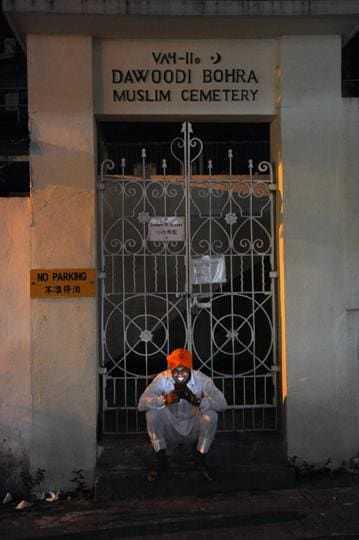 Cultural and religious diversity is characteristic of Hong Kong. After praying at the nearby gurdwara, a Sikh man pauses to talk on his mobile phone in front of a Dawoodi Bohra cemetery in the city's Happy Valley. The first burial here dates back to 1828.