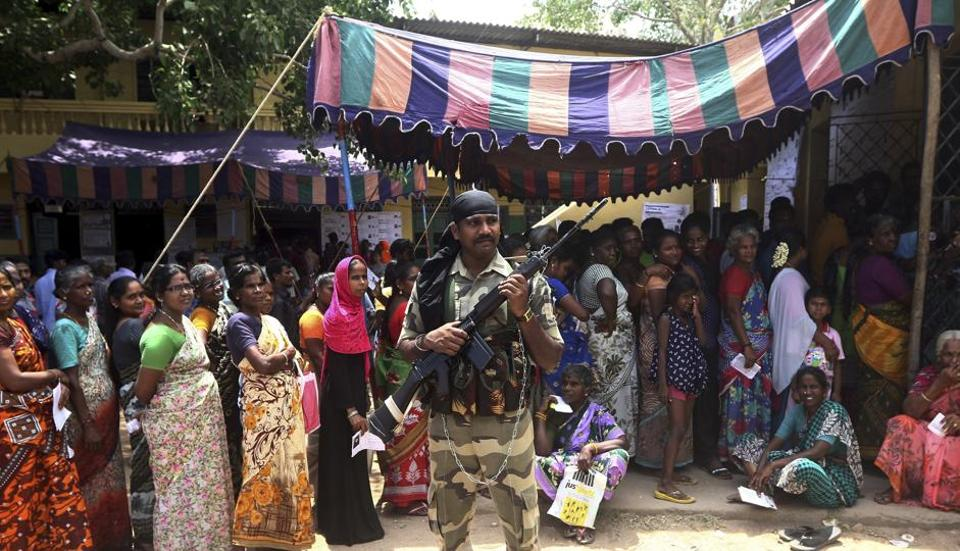 A soldier stands guard as Indians wait in a queue to cast their votes during the second phase of general elections in Chennai, India, Thursday, April 18, 2019.