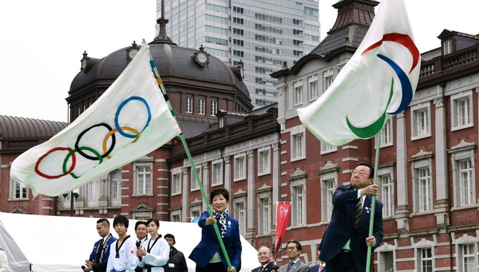 Tokyo Governor Yuriko Koike (C) and Yoshitaka Sakurada, Minister for the Tokyo Olympic and Paralympic Games, wave the flags during the final event of the Tokyo 2020 Olympic Flag and Paralympic Flag Tour,