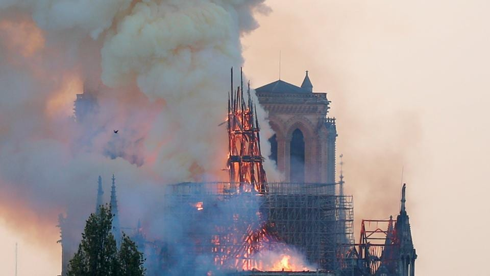 Smoke rises from the burning spire on the roof at the Notre-DameCathedral after a fire broke out, in Paris, France April 15, 2019. Picture taken April 15, 2019. REUTERS/Charles Platiau - RC198DB5D280