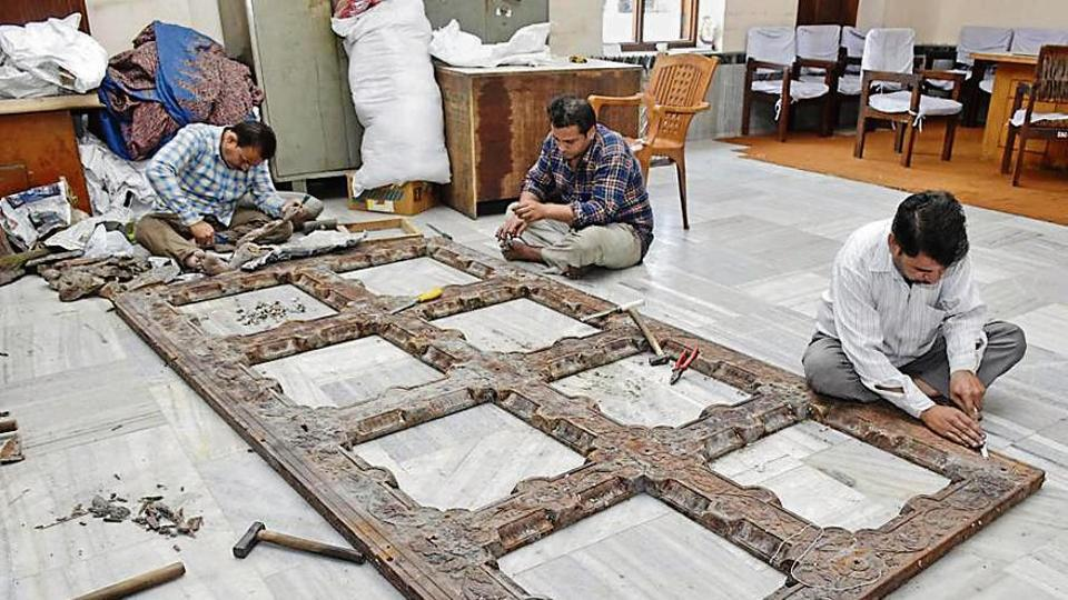 Workers preparing gates of Durgiana Temple with 200-kg silver at the temple complex in Amritsar, Thursday, April 18, 2019.