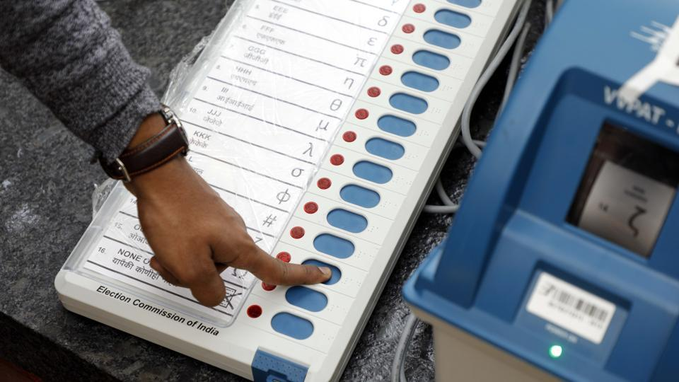 An election commission official checks an EVM.