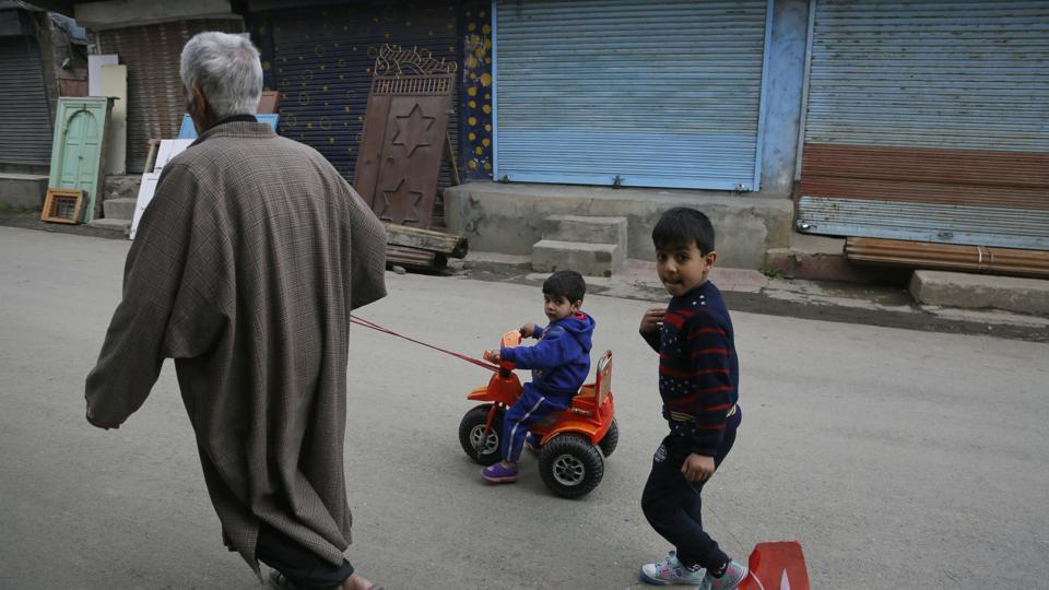 An elderly man pulls a child on a tricycle during a strike called on the second phase of general elections in Srinagar, Jammu and Kashmir. (Mukhtar Khan / AP)