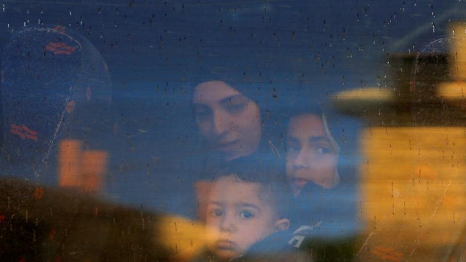 The wife and children of Palestinian prisoner Ayman Ghareeb, who is held in an Israeli jail, look out of a bus window on their way to visit him in the jail, as Palestinians mark Prisoners' Day, in Tubas in the Israeli-occupied West Bank. (Raneen Sawafta / REUTERS)