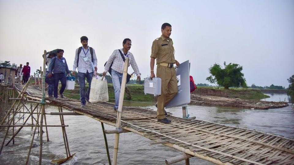 Election staff carry VVPAT machines and an EVM as they cross a bamboo bridge to reach remote polling stations ahead of second phase of general elections, at Soraijuria village in Nagaon, Assam. (PTI)