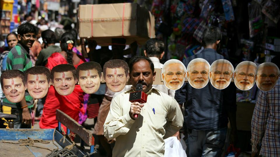 Anand Kumar Bowmick, a social activist, carries masks of Prime Minister Narendra Modi and President of Congress party Rahul Gandhi through a busy street as he appeals people to vote in the second phase of general election in Chennai, Tamil Nadu. (P. Ravikumar / REUTERS)