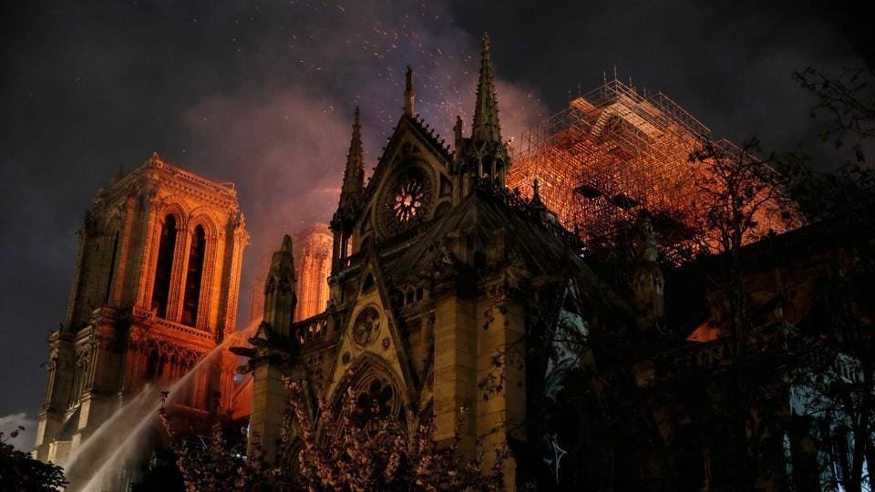 Sparks fill the air as Paris Fire brigade members spray water to extinguish flames as the Notre Dame Cathedral burns in Paris, France. (Philippe Wojazer / REUTERS)