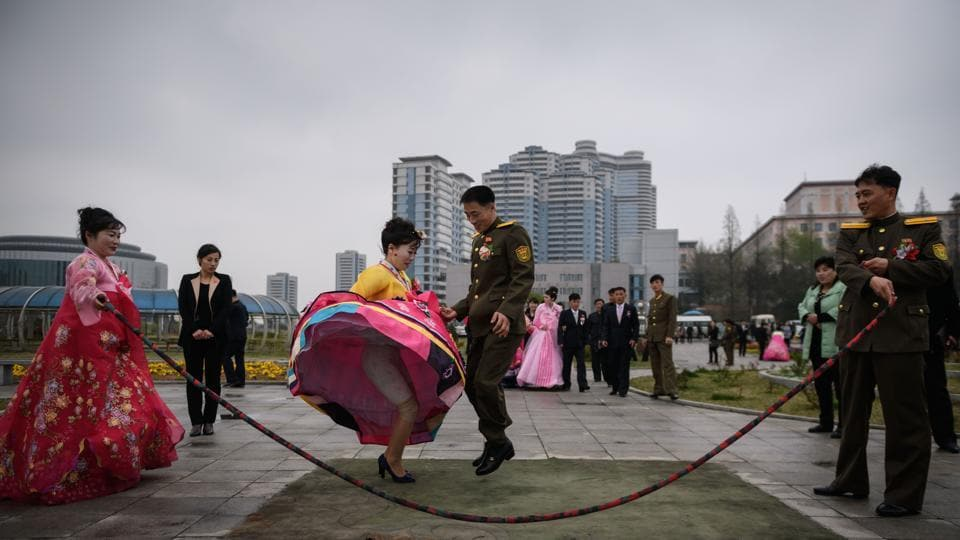 A bride and groom jump over a skipping rope as they pose during a wedding photo shoot at a park in Pyongyang, North Korea. (Ed Jones / AFP)
