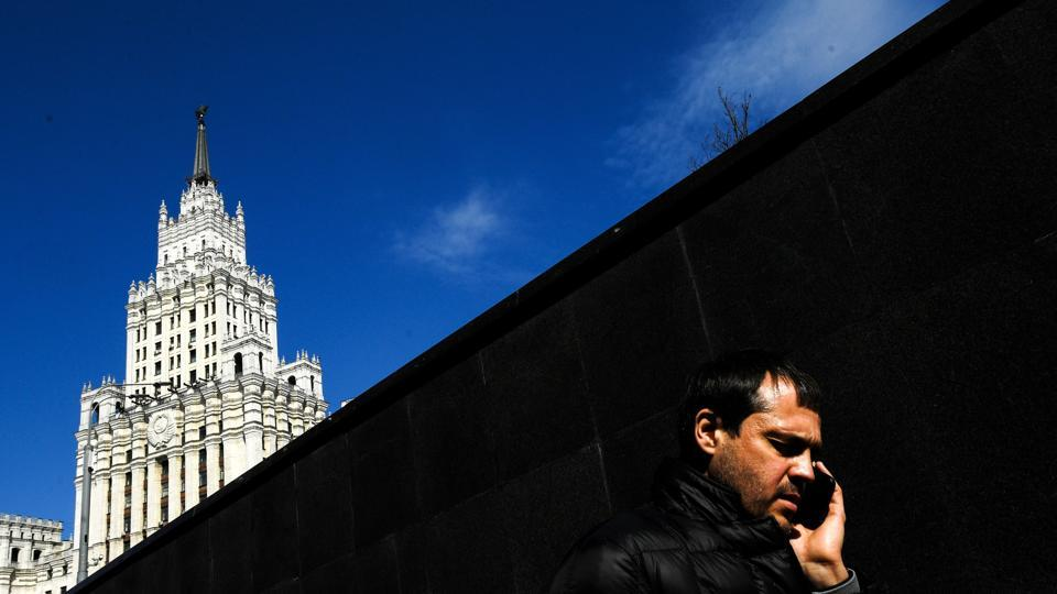 A man speaks on a mobile phone while walking out of an underground passage on a sunny day in Moscow, Russia. (Kirill Kurdyavtsev / AFP)
