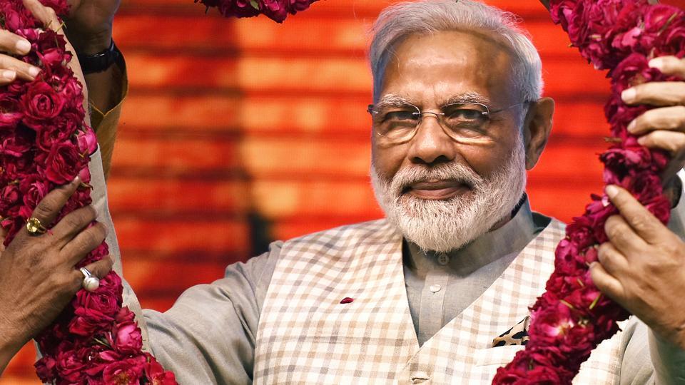 Prime Minister Narendra Modi being garlanded at 'Traders Sammelan' at Talkatora Stadium, in New Delhi, on Friday, April 19, 2019.
