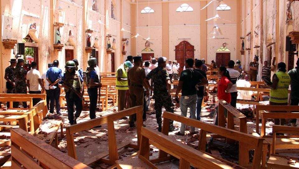 Sri Lankan security personnel walk past dead bodies covered with blankets amid blast debris at St Sebastian's Church. At least nine foreigners were among 160 people killed in eight near simultaneous and coordinated explosions that rocked three churches and three luxury hotels frequented by tourists in Sri Lanka on Easter Sunday, in one of the deadliest blasts in the country's history. (STR / AFP)