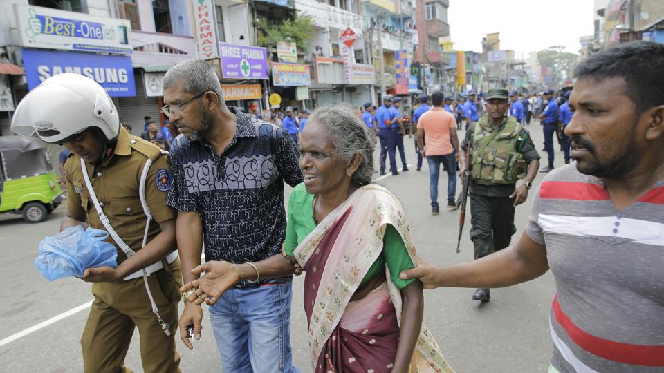 Sri Lankan elderly woman is helped near St. Anthony's Shrine after a blast in Colombo on Sunday after the multiple explosions that rocket the city.