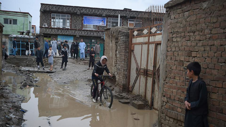 Kobra Samim rides her bicycle through a flooded street in Kabul. Before being toppled by the US invasion of 2001, the Taliban governed Afghanistan for nearly five years with a strict interpretation of sharia law. Women were confined to their homes, forced to wear burqas and forbidden from going to school. Some were publicly stoned to death on flimsy allegations of adultery. (Wakil Kohsar / AFP)