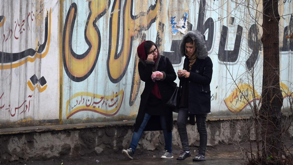 Afghan girls walk next to graffitis on a wall in Kabul. The United States is holding direct talks with Taliban leaders -- all men --- in a bid to forge a peace deal. Two Afghan women were invited to informal talks in Moscow in February between the Taliban and Afghan representatives, but their presence was very peripheral.  (Wakil Kohsar / AFP)