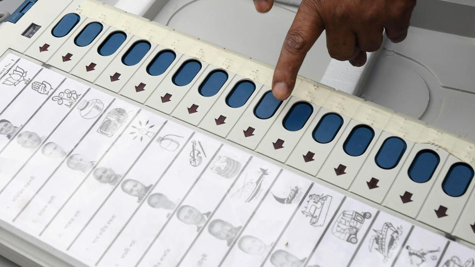 An election official examines an EVM at a distribution centre.