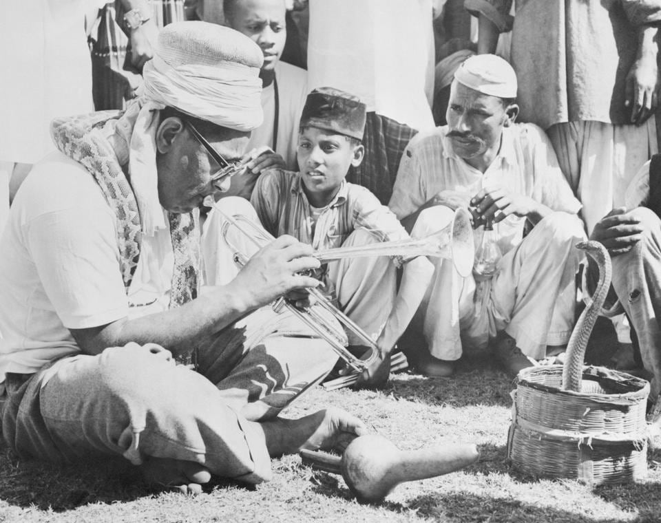 """Jazz legend Dizzy Gillespie charms a snake with his trumpet during a trip to Karachi in 1956. """"Pakistanis and cobra found him irresistible,"""" says the original caption."""