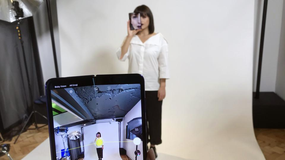 In this April 16, 2019, file photo, a model holds a Samsung Galaxy Fold smart phone to her face, during a media preview event in London. Samsung is pushing back this week's planned public launch of its highly anticipated folding phone after reports that reviewers' phones were breaking. The company had been planning to release the Galaxy Fold on Friday. Instead, it says it will to run more tests and announce a new launch date in the coming weeks.