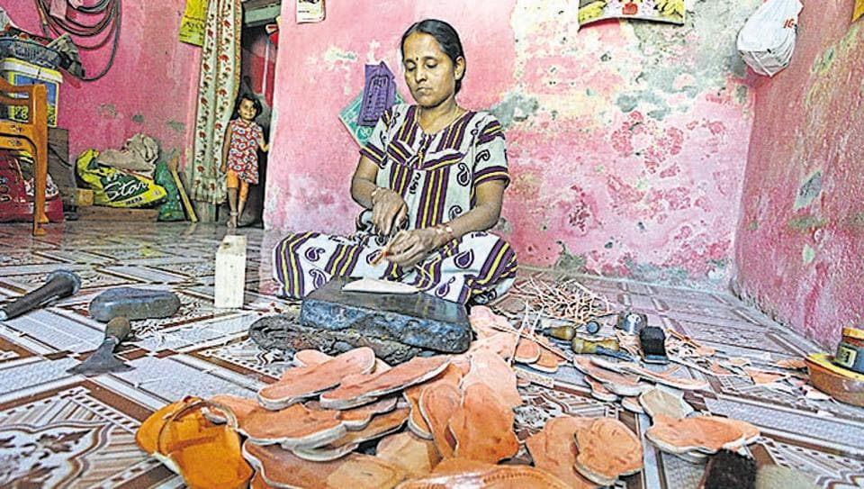 Woman makes Kolhapuri chappals in Kolhapur. Number of chappals being made daily has reduced.