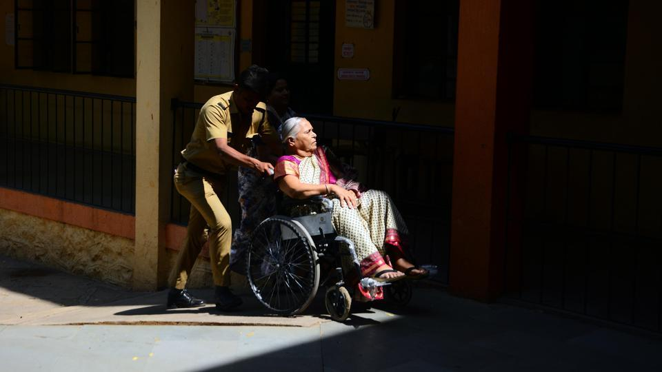 A police personnel helps an elderly person by pushing her wheel chair over a slope during voting in Pune, Maharashtra. (Shankar Narayan / HT photo)