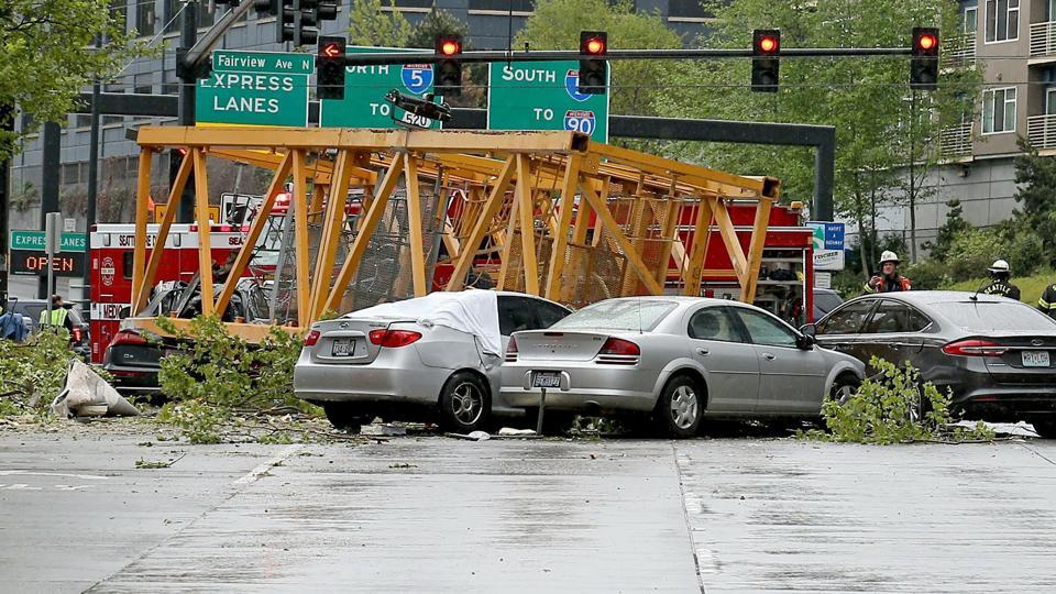 Four people were killed and three wounded when a construction crane collapsed Saturday in downtown Seattle, pinning five cars underneath.