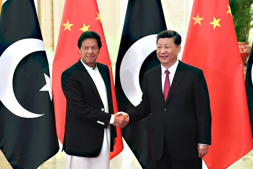 China's President Xi Jinping (R) shakes hands with Pakistan's Prime Minister Imran Khan (L) before their meeting at the Great Hall of the People in Beijing on April 2019.