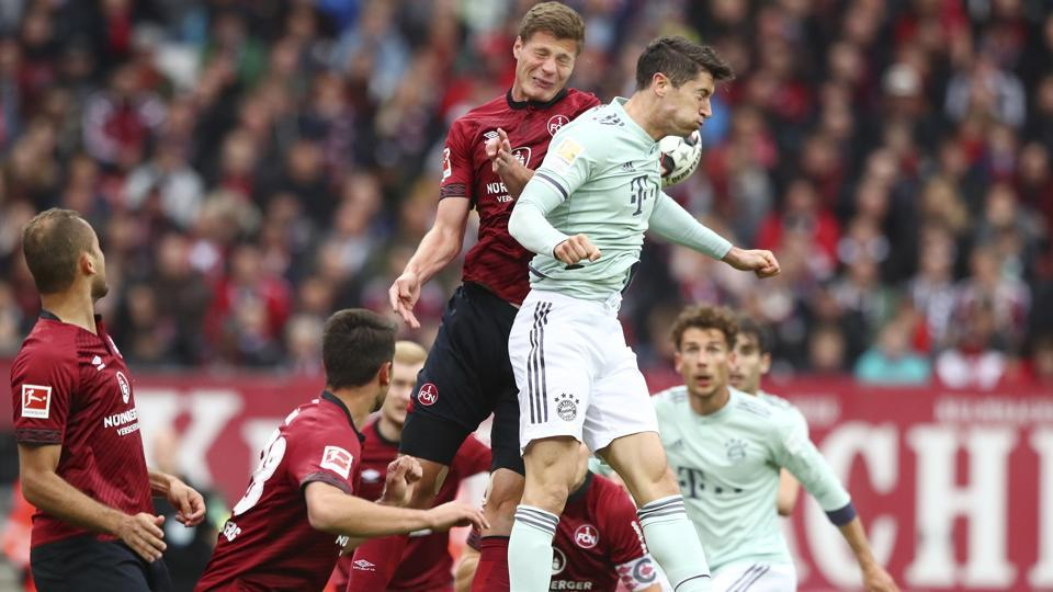 Bayern's Robert Lewandowski, top right, jumps for the ball with Nuremberg's Patrick Erras, top left.