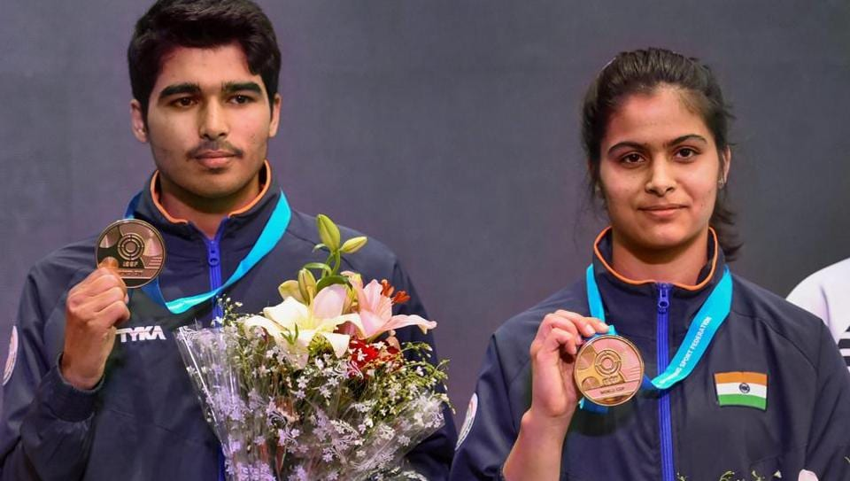 India's Manu Bhaker (R) and Saurabh Chaudhary pose for photographs with their gold medals after winning the 10m Air Pistol Mixed Team event at the ISSF World Cup