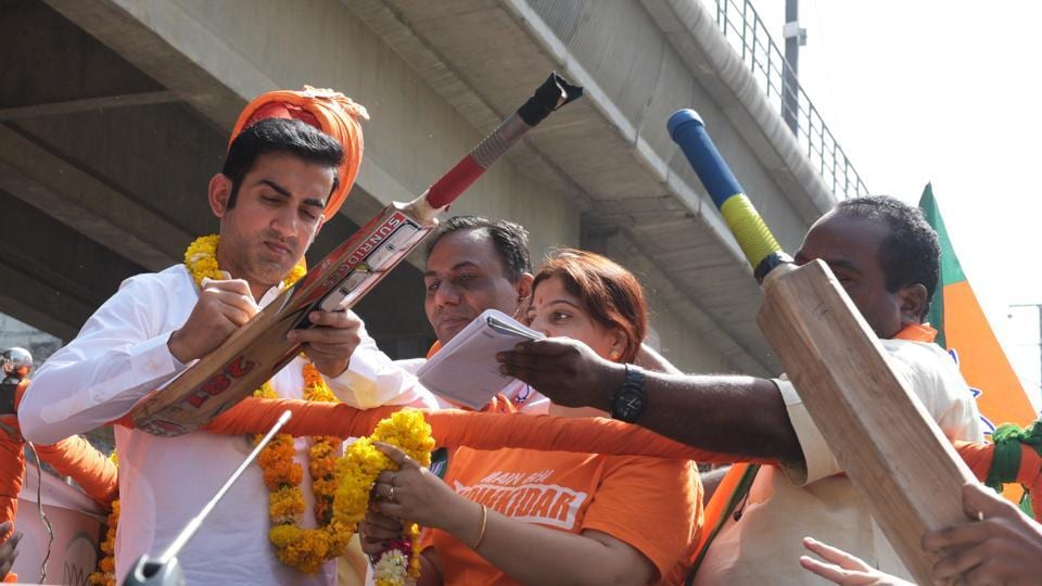 Cricketer-turned-politician BJP candidate from East Delhi Loksabha constituency Gautam Gambhir signs his autograph during the road show at New Ashok Nagar to Trilokpuri in New Delhi.