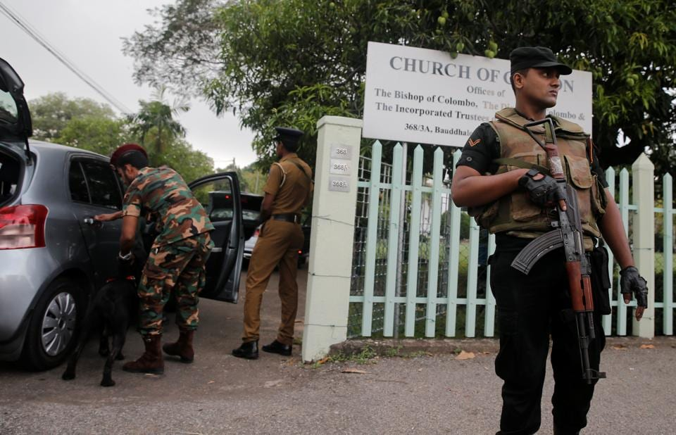 Security personnel stand guard outside an Anglican church before a service, a week after a string of suicide bomb attacks across the island on Easter Sunday.