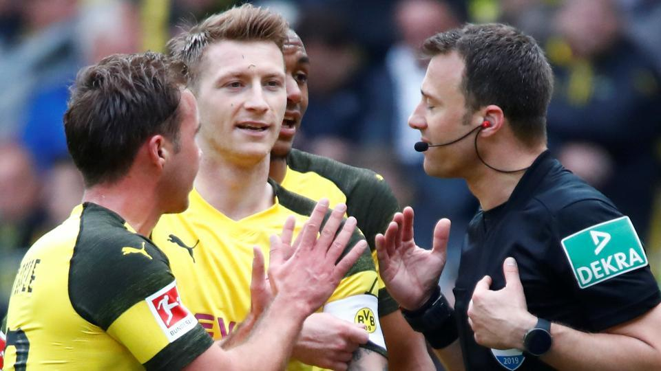 Borussia Dortmund's Marco Reus and Mario Goetze argue with referee Felix Zwayer following a red card against Reus.