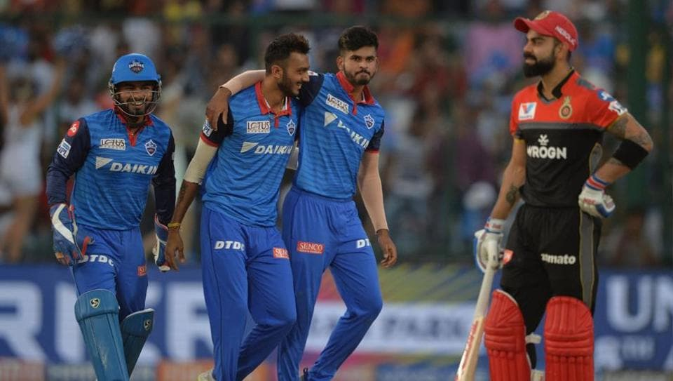 Delhi Capitals bowler Axar Patel (C) celebrates with his team captain Shreyas Iyer (R) and wicketkeeper Rishabh Pant (L) after he dismissed Royal Challengers Bangalore cricketer and team captain Virat Kohli