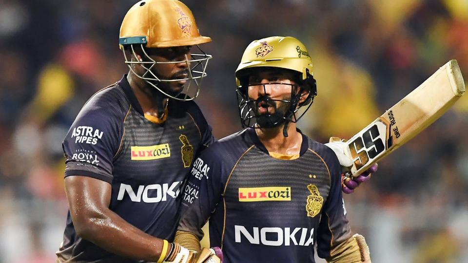 Kolkata Knight Riders' cricketer Andre Russell (L) talks with captain Dinesh Karthik.