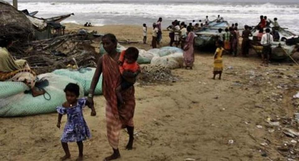 A woman evacuates the coast with her children in Ganjam district, Odisha following a cyclone alert.