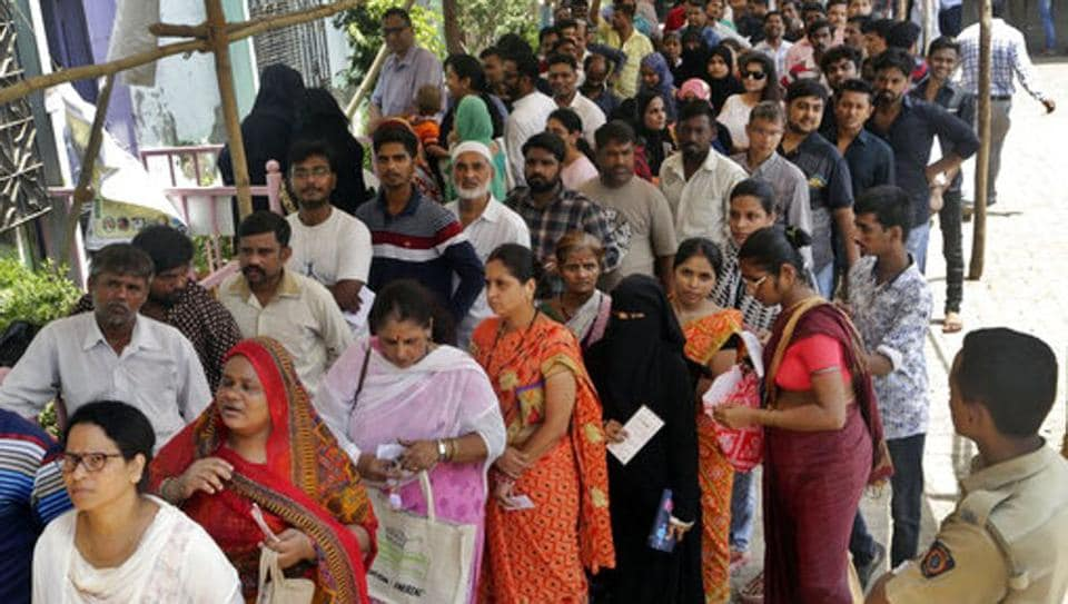 People stand outside a polling booth to cast their votes in Mumbai, India, Monday, April 29, 2019.