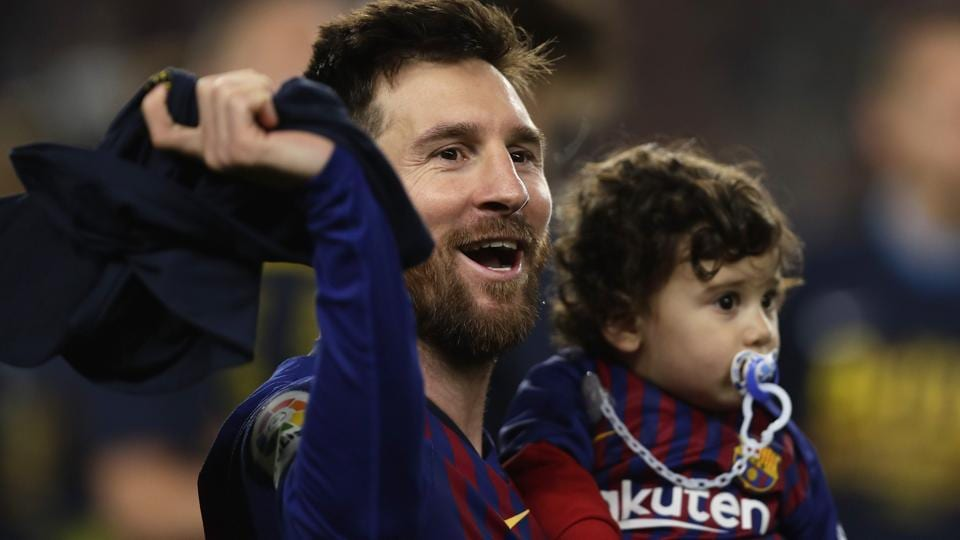 Barcelona forward Lionel Messi holds his son as celebrates winning the Spanish League title.