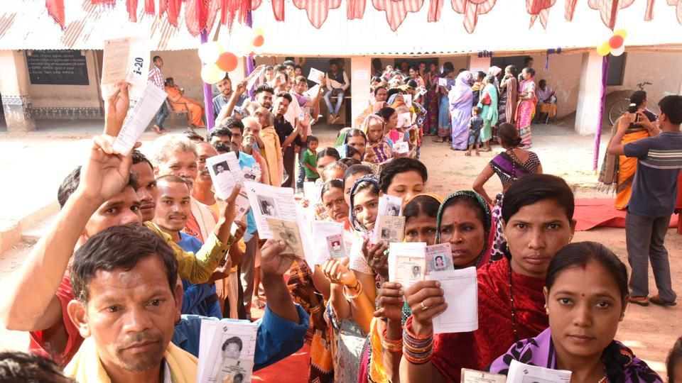 Voters show their identity cards as they stand in queues to cast their votes during the second phase of the general elections at a polling station, Kandhamal district, Odisha,  April 18, 2019