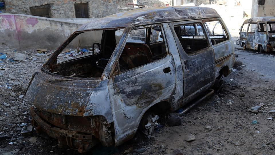 Charred cars are scattered on a street after recent heavy clashes between pro-government militias in Yemen's southern city of Taez on Monday.