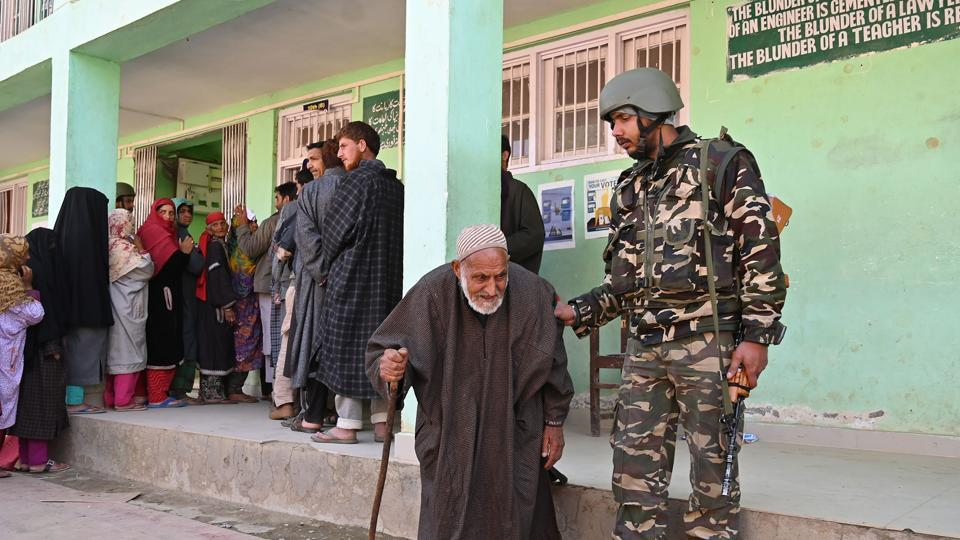 A security personnel helps an elderly Kashmiri voter after he voted during the fourth phase of  Lok Sabha elections at Damhal Hanjipora, Kulgam district, Jammu and Kashmir, on April 29, 2019.