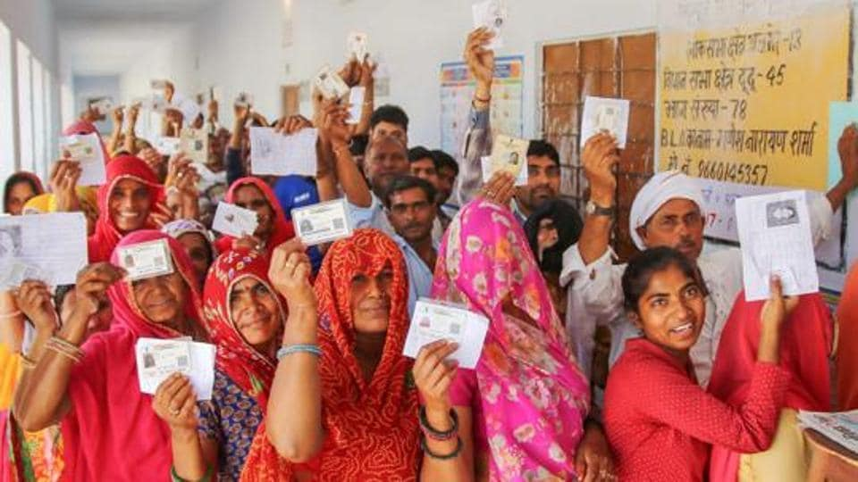 Election Results 2019: People show their voter's identity cards as they wait in queues to cast their votes at a polling station
