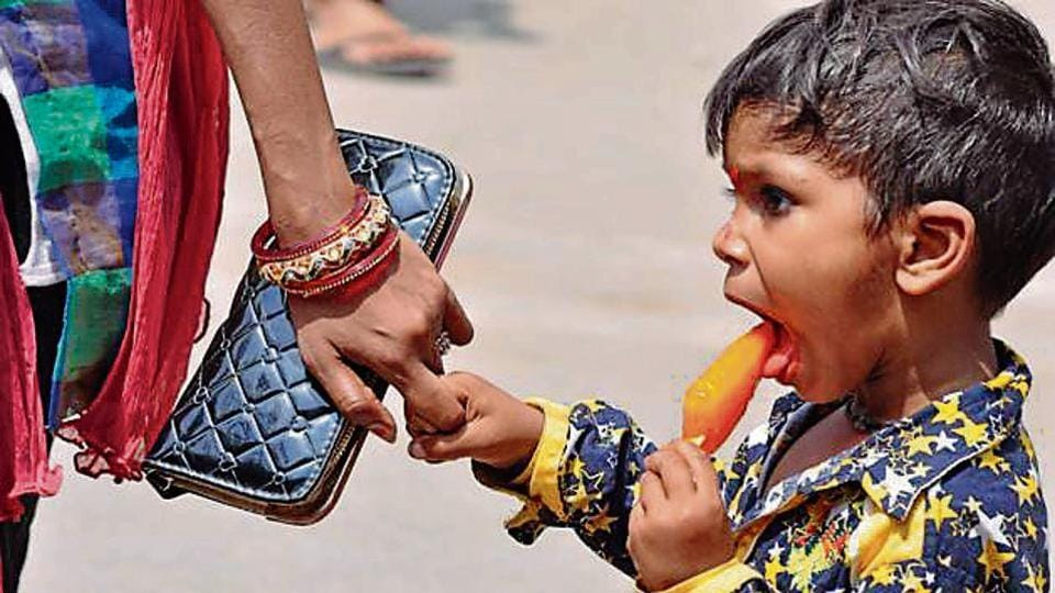 A child relishes an ice cream to beat the heat as temperatures in most parts of the state hovered above 40-degree mark.